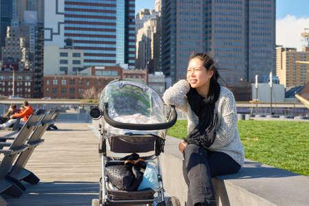 NEW YORK - 17 MARS 2016: une femme se repose au Quai 15 pendant la journée. Pier 15 est situé à l'est de South Street et FDR Drive à Lower Manhattan, New York. Éditoriale