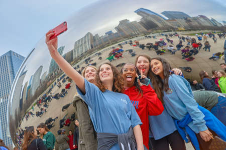 CHICAGO, IL - CIRCA MARCH, 2016: women taking a selfie near Cloud Gate. Cloud Gate is a public sculpture by Indian-born British artist Anish Kapoor. Editorial