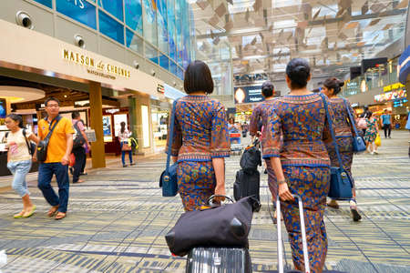 싱가포르 - 창이아 공항에서 싱가포르 항공 승무원 2016 년 8 월 8 일. 창이 공항은 싱가포르의 주요 민간 공항입니다.
