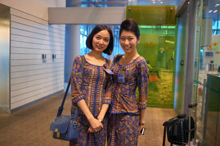 SINGAPORE - CIRCA NOVEMBER, 2015: indoor portrait of two pretty Singapore Airlines stewardesses at Changi Aiport. 新聞圖片