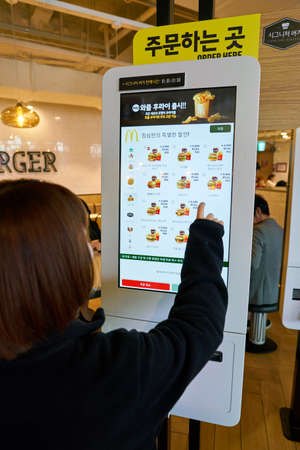 SEOUL, SOUTH KOREA - CIRCA MAY, 2017: woman use McDonalds ordering kiosk. McDonalds is an American hamburger and fast food restaurant chain. Редакционное