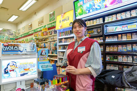 SEOUL, SOUTH KOREA - CIRCA MAY, 2017: indoor portrait of worker at 7-Eleven convenience store. 7-Eleven is an international chain of convenience stores. Editorial