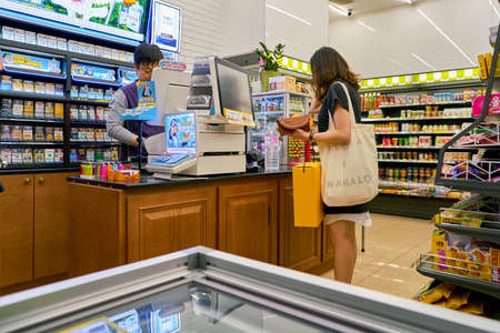SEOUL, SOUTH KOREA - CIRCA MAY, 2017: woman paying at CU convenience store. CU is a convenience store franchise chain in South Korea. Editorial