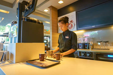 SHENZHEN, CHINA - CIRCA OCTOBER, 2015: young pretty barista at McCafe preparing coffee. McCafe is a coffee house style food and drink chain, owned by McDonalds.