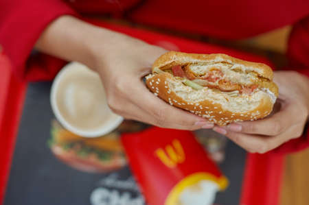 KALININGRAD, RUSSIA - CIRCA OCTOBER, 2017: woman hands hold hamburger at McDonald's restaurant.