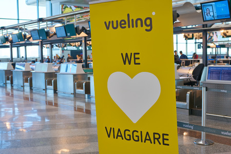MILAN MALPENSA, ITALY - CIRCA NOVEMBER, 2017: close up shot of vueling sign at check-in area in Milan-Malpensa airport, Terminal 1. Editöryel