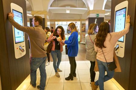 ROME, ITALY - CIRCA NOVEMBER, 2017: customers use self-ordering kiosks at McDonald's restaurant in Rome.
