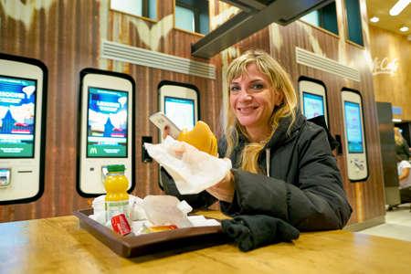 MILAN, ITALY - CIRCA NOVEMBER, 2017: woman eat at a McDonald's restaurant in Milan.