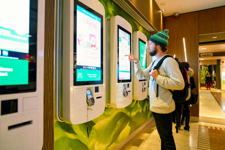 MILAN, ITALY - CIRCA NOVEMBER, 2017: customer at a McDonald's store place orders and pay through self ordering kiosk. Editoriali