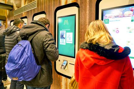 MILAN, ITALY - CIRCA NOVEMBER, 2017: customers at a McDonalds store place orders and pay through self ordering kiosks. Editorial