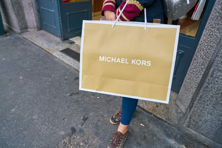 MILAN, ITALY - CIRCA NOVEMBER, 2017: a woman stand with a Michael Kors branded shopping bag in Milan.