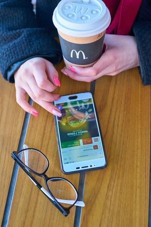 KALININGRAD, RUSSIA - CIRCA APRIL, 2018: woman use smartphone at McDonald's restaurant in Kaliningrad.