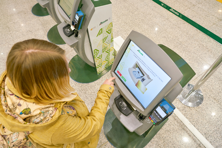 ROME, ITALY - CIRCA NOVEMBER, 2017: woman use self check-in kiosks in Fiumicino International Airport Leonardo da Vinci