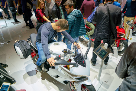 MILAN, ITALY - NOVEMBER 11, 2017: a visitor try out a motorcycle at the EICMA 2017 - 75th International Motorcycle Exhibition. Editorial