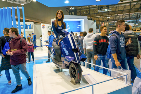 MILAN, ITALY - NOVEMBER 11, 2017: a model poses with a scooter for the visitors during the EICMA 2017 - 75th International Motorcycle Exhibition.