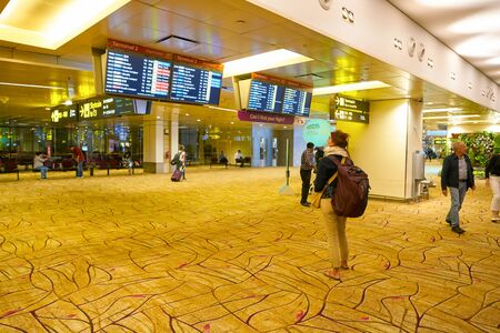 SINGAPORE - CIRCA APRIL, 2019: woman looking at timetable departure board in Singapore Changi Airport. Redactioneel