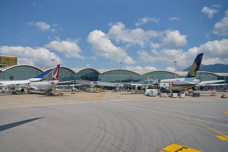 HONG KONG, CHINA - CIRCA ABRIL, 2019: Cathay Dragon y Singapore Airlines aviones sobre asfalto en el Aeropuerto Internacional de Hong Kong.