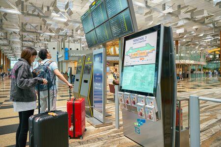 SINGAPORE - CIRCA APRIL, 2019: passengers looking at flight schedule monitors at Singapore Changi International Airport.
