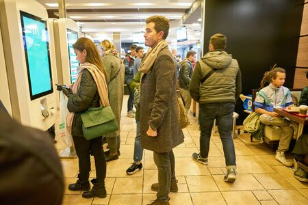 MOSCOW, RUSSIA - CIRCA OCTOBER, 2018: people use self-ordering kiosks at McDonald's restaurant.