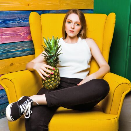 full face: Fruit fashion girl Fruit fashion girl sitting in a yellow chair. Young girl holds pineapple. Striped colorful background. Full face. Bright juicy picture Stock Photo