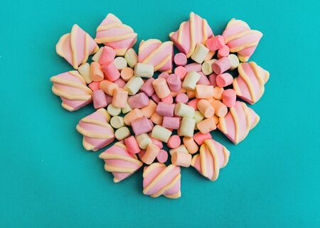 Marshmallows Background or texture of colorful mini marshmallows Multicolored marshmallows are lying in the shape of a heart on a blue background