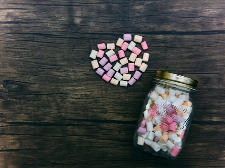 spongy: Marshmallows in a jar Multicolored marshmallows in a clear glass jar on a wooden table and marshmallows are in the form of heart