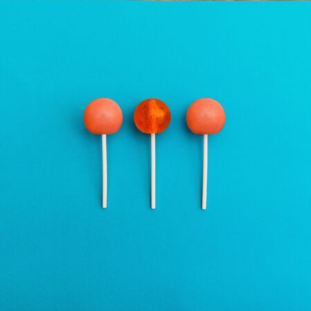 Three orange round lollipops are lying on a light blue background Trendy bright photo in modern pop art style Top view Stock Photo