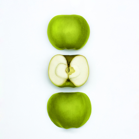 Green apples Top view Fresh granny smith Three different halves of green apples are lying vertically in a row on a white background Flat lay mockup with text space Stock Photo