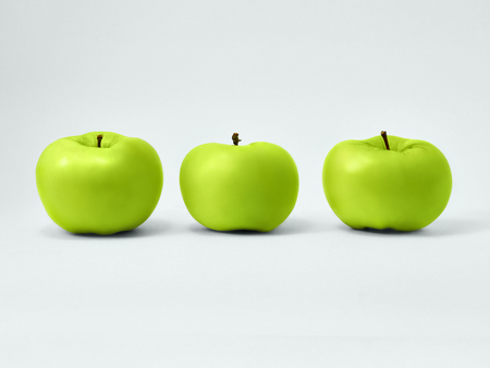 Isolated green apples Fresh granny smith Three juicy green apples are standing upright in a row on a white background Isolated fruits photo Stock Photo