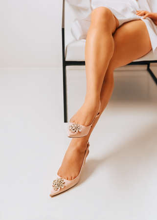 Female legs beauty Photo with copy space Girl with tan skin in light pink atlas shoes with decoration is sitting in white room
