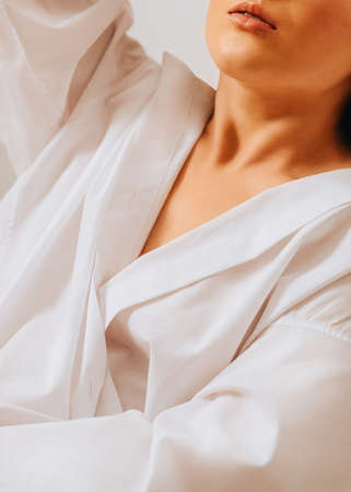 Bedroom morning Close up photo of resting woman Unrecognizable girl with tan skin in white cotton shirt on white backdrop Archivio Fotografico