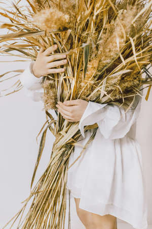Loving nature Conceptual photo with copy space Girl in white bohemian dress is holding armful of dry fields plants Archivio Fotografico
