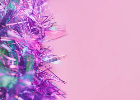 Tinsel Close up photo with copy space Shiny lilac tinsel on pink background Template for posters and banners Archivio Fotografico