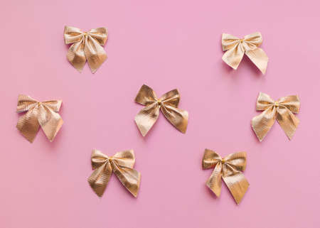 Gold bows Top view photo in minimal style Pattern with decorative gift bows on pink background