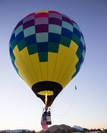 Montague, California, USA-September 25, 2015: A hot air balloon soars above the crowds below in northern California skies during the Montague Hot Air Balloon Fair. Imagens - 48944452