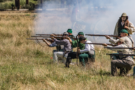 infantryman: Portola, California, United States-July 4, 2015:Southern infantryman fires during a skirmish with Union soldiers at a Civil War reenactment.