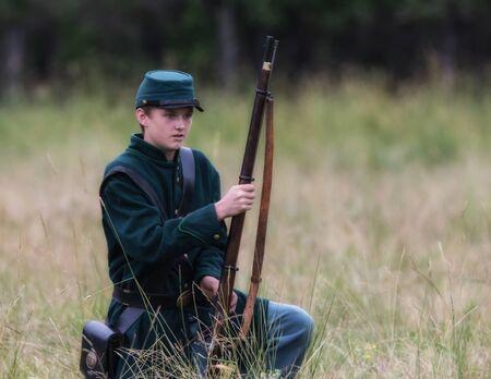 reenactor: Confederate Civil War Reenactor during a battle in Graeagle, California.