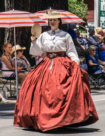 belle: Graeagle, California, USA- July 5, 2015: A female member of a Civil War reenactment group dressed as a southern belle walks down the parade route at the Mohawk Valley Independence Day Celebration. Editorial