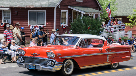 chevy: Graeagle, California, USA- July 5, 2015: A customized Chevy Impala drives down the parade route as the driver and passenger wave to the crowd during the Mohawk Valley Independence Day Celebration.