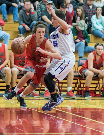 basketball game: A Foothill player red makes a drive into the key during a basketball game in Redding, California