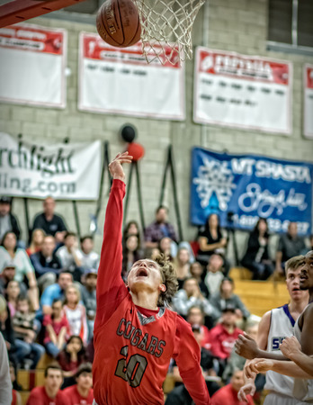 basketball game: A Foothill player red throws up a shot  during a basketball game in Redding, California