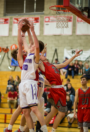 Players from Shasta white and Foothill fight for a rebound   during a basketball game in Redding, California.