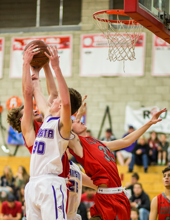 basketball game: Players from Shasta white and Foothill fight for a rebound   during a basketball game in Redding, California.