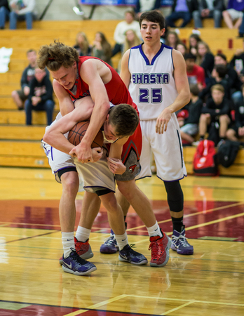basketball game: A Shasta player white and a Foothill player fight for the ball  during a basketball game in Redding, California.