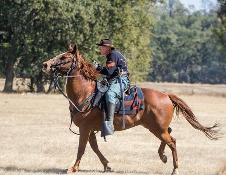 advances: Union cavalry Scout advances towards the  enemy at a Civil War reenactment, Anderson, California. Editorial