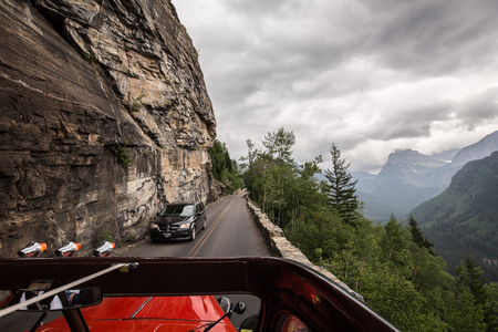 await: Glacier National Park, Montana, USA-July 11, 2015: The famous Red Bus vehicles of the parks service await passengers to tour Going to the Sun Road inside the park.