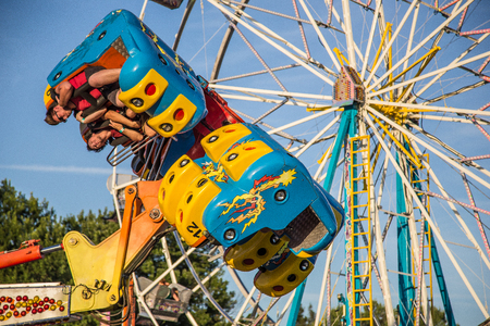 Anderson, California, USA- June 17, 2015: Fair goers enjoy being tossed around and thrown upside down on this popular ride at the Shasta County Fair.