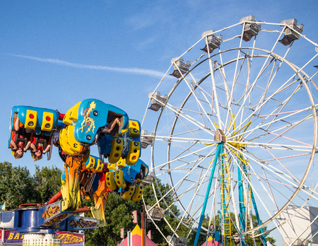 Anderson, California, USA- June 17, 2015: Fair goers enjoy the carnival ride Freak Out at the Shasta County FairThe Freak Out is a pendulum shaped ride that is very popular.