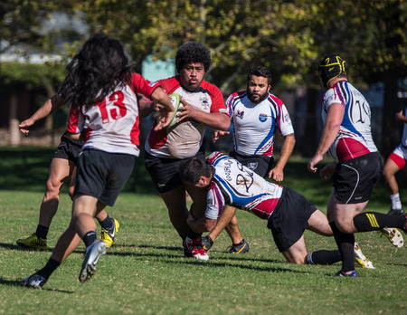 mighty: Hooligan Highwaymen players tackle a Chico Mighty Oak  at a rugby tournament in Redding, California. Editorial