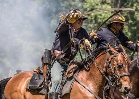 vestidos de epoca: exploradores de la Unión atacan con las espadas desenvainadas Cannon peleas de la tripulación de vuelta en Dog Island reconstrucción de la guerra civil, Red Bluff, California Editorial